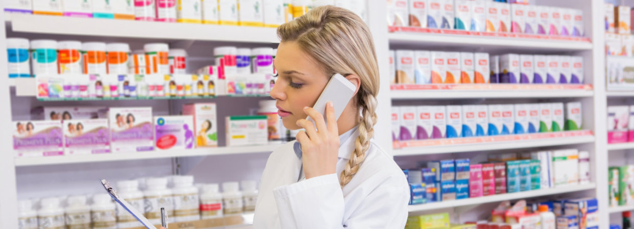 pharmacist looking at a list while calling a customer